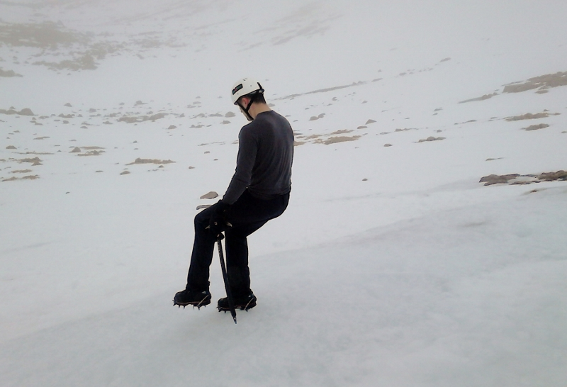 Winter skills descending a ice slope with crampons using the flat foot technique