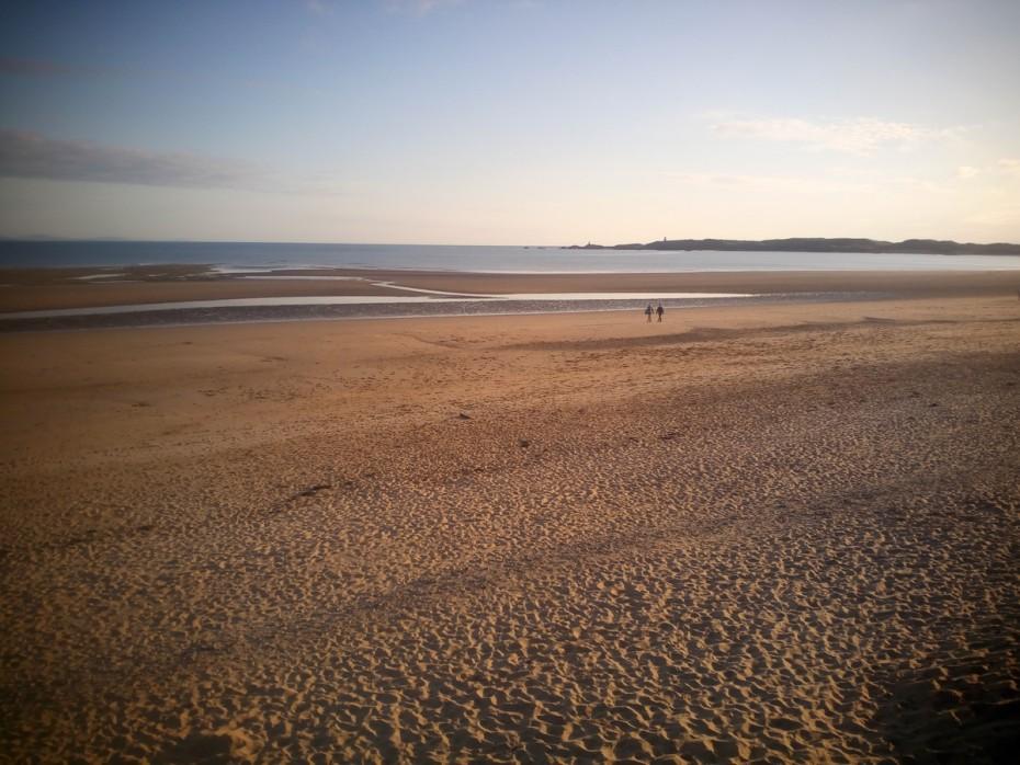 Walking on the Anglesey coastal path on Newborough beach looking towards Ynys Llanddwyn