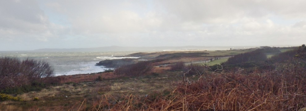 On the Anglesey Coastal Path looking towards Holyhead bay with the sea crashing in against the rocks