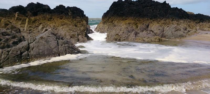 Anglesey Coastal Path  Llanddwyn Island with the sea crashing in on to the beach