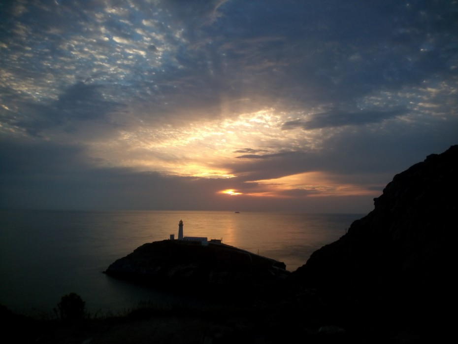Walking on the Anglesey coastal path The light house at sunset. A beautiful view