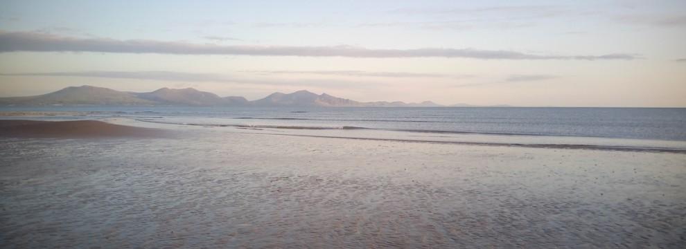 Walking on the Anglesey coastal path on Newborough beach beautiful mountains of Snowdonia