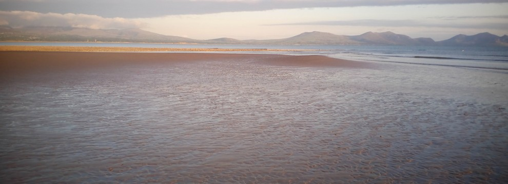 Walking on the Anglesey coastal path on Newborough beach golden sands