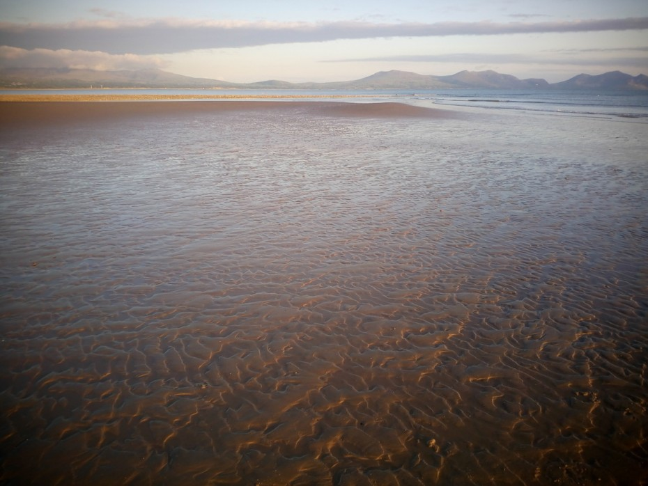 Walking on the Anglesey coastal path on Newborough beach looking across to the Snowdonia mountains