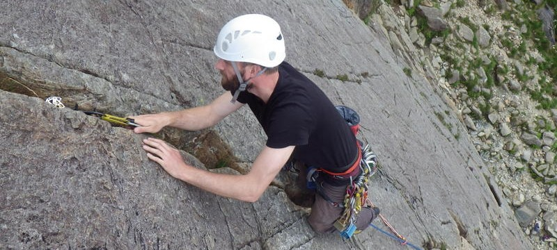 Trad rock climbing placing cams