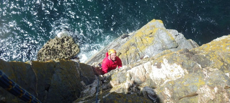 climbing on the South stack sea cliffs on the crux of lighthouse arete ..gaining the overhanging corner