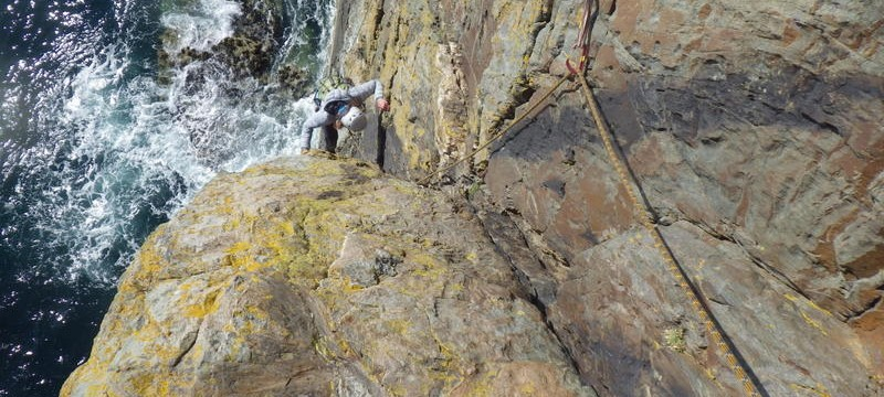 Rock climbing on the South stack sea cliffs gaining entry into the corner from the wall