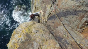 Rock climbing on the South stack sea cliffs Bridget bridging out to take the weight off the arms
